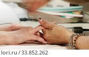 Купить «Female manicurist processes the client's nails with a nail file in a nail salon», видеоролик № 33852262, снято 26 мая 2020 г. (c) Алексей Кузнецов / Фотобанк Лори