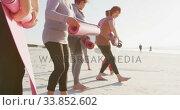 Купить «Multi-ethnic group of women folding sport mats on the beach and blue sky background», видеоролик № 33852602, снято 15 октября 2019 г. (c) Wavebreak Media / Фотобанк Лори