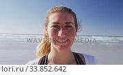 Купить «Caucasian woman looking at camera and smiling on the beach and blue sky background», видеоролик № 33852642, снято 15 октября 2019 г. (c) Wavebreak Media / Фотобанк Лори