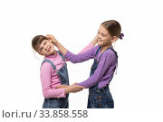 Старшая девочка таскает за ухо младшую, изолировано. Стоковое фото, фотограф Иванов Алексей / Фотобанк Лори