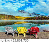 Rocky Mountains of Canada. Three comfortable multi-colored deck chairs stand by the Piramid lake. Concept of ecological, active and photo-tourism. Стоковое фото, фотограф Zoonar.com/kavram / easy Fotostock / Фотобанк Лори