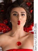 Купить «Brunette in red with emotional lips on bed with petals», фото № 33865086, снято 15 мая 2020 г. (c) Гурьянов Андрей / Фотобанк Лори