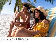 Купить «Caucasian couple  sitting on deck chairs at the beach», фото № 33866070, снято 25 февраля 2020 г. (c) Wavebreak Media / Фотобанк Лори