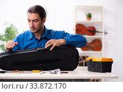 Купить «Young male repairman repairing violin», фото № 33872170, снято 25 октября 2019 г. (c) Elnur / Фотобанк Лори