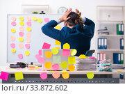 Купить «Young male employee in conflicting priorities concept», фото № 33872602, снято 4 октября 2019 г. (c) Elnur / Фотобанк Лори