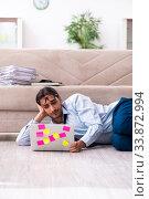 Купить «Young male businessman working at home», фото № 33872994, снято 9 августа 2019 г. (c) Elnur / Фотобанк Лори