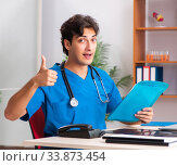 Купить «Young handsome doctor radiologyst working in clinic», фото № 33873454, снято 10 августа 2018 г. (c) Elnur / Фотобанк Лори