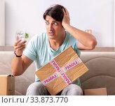 Купить «Man opening fragile parcel ordered from internet», фото № 33873770, снято 4 июля 2018 г. (c) Elnur / Фотобанк Лори
