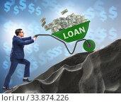 Businessman pushing wheelbarrow uphill in debt loan concept. Стоковое фото, фотограф Elnur / Фотобанк Лори