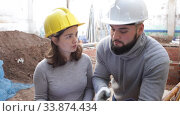 Two confident engineers discussing blueprint while standing at construction site. Стоковое видео, видеограф Яков Филимонов / Фотобанк Лори