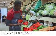 Confident African American seller in black apron arranging fresh red peppers on greengrocery counter. Стоковое видео, видеограф Яков Филимонов / Фотобанк Лори