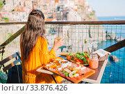 Купить «Beautiful woman on breakfast at outdoor cafe with amazing view in Cinque Terre», фото № 33876426, снято 11 июня 2017 г. (c) Дмитрий Травников / Фотобанк Лори