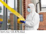 Купить «healthcare worker sealing door with caution tape», фото № 33876822, снято 24 апреля 2020 г. (c) Syda Productions / Фотобанк Лори