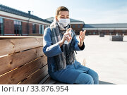 woman in mask spraying hand sanitizer outdoors. Стоковое фото, фотограф Syda Productions / Фотобанк Лори