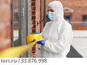 Купить «healthcare worker sealing door with caution tape», фото № 33876998, снято 24 апреля 2020 г. (c) Syda Productions / Фотобанк Лори