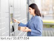 Купить «smiling woman with box at automated parcel machine», фото № 33877034, снято 22 апреля 2020 г. (c) Syda Productions / Фотобанк Лори