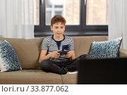 Купить «boy with gamepad playing video game at home», фото № 33877062, снято 10 апреля 2020 г. (c) Syda Productions / Фотобанк Лори