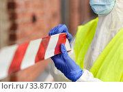 Купить «healthcare worker sealing door with caution tape», фото № 33877070, снято 24 апреля 2020 г. (c) Syda Productions / Фотобанк Лори