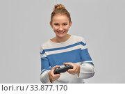 Купить «happy teenage girl with gamepad playing video game», фото № 33877170, снято 26 февраля 2020 г. (c) Syda Productions / Фотобанк Лори