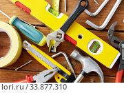 Купить «different work tools on wooden boards background», фото № 33877310, снято 26 ноября 2019 г. (c) Syda Productions / Фотобанк Лори