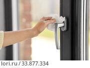 Купить «woman cleaning window handle with wet wipe», фото № 33877334, снято 24 апреля 2020 г. (c) Syda Productions / Фотобанк Лори