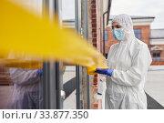 Купить «healthcare worker sealing door with caution tape», фото № 33877350, снято 24 апреля 2020 г. (c) Syda Productions / Фотобанк Лори