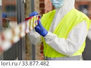 Купить «healthcare worker sealing door with caution tape», фото № 33877482, снято 24 апреля 2020 г. (c) Syda Productions / Фотобанк Лори