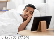 sleepy indian man looking at tablet pc in bed. Стоковое фото, фотограф Syda Productions / Фотобанк Лори