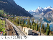 Railway along the shore of lake Lucerne near the town Sisikon. View of the snow-covered Alps. Canton of Uri, Switzerland. (2018 год). Стоковое фото, фотограф Bala-Kate / Фотобанк Лори