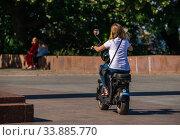 Купить «Girl rides an electric bike in the park», фото № 33885770, снято 16 сентября 2019 г. (c) Sergii Zarev / Фотобанк Лори