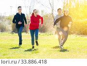 Happy teenage friends chasing each other on green meadow. Стоковое фото, фотограф Яков Филимонов / Фотобанк Лори
