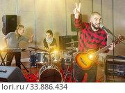 Купить «Guy guitar player and singer practicing with band members in re», фото № 33886434, снято 26 октября 2018 г. (c) Яков Филимонов / Фотобанк Лори