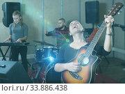 Купить «Adult guitar player and singer with band», фото № 33886438, снято 26 октября 2018 г. (c) Яков Филимонов / Фотобанк Лори