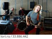 Купить «excited girl rock singer with guitar during rehearsal», фото № 33886442, снято 26 октября 2018 г. (c) Яков Филимонов / Фотобанк Лори
