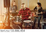Expressive drummer with his bandmates practicing in rehearsal ro. Стоковое фото, фотограф Яков Филимонов / Фотобанк Лори
