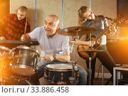 Купить «Expressive drummer with his bandmates practicing in rehearsal ro», фото № 33886458, снято 26 октября 2018 г. (c) Яков Филимонов / Фотобанк Лори