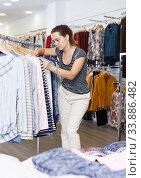 Купить «Woman choosing new clothes in showroom», фото № 33886482, снято 10 октября 2018 г. (c) Яков Филимонов / Фотобанк Лори