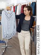 Woman shopping in clothing boutique. Стоковое фото, фотограф Яков Филимонов / Фотобанк Лори