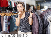 Купить «Woman choosing new coat in showroom», фото № 33886510, снято 10 октября 2018 г. (c) Яков Филимонов / Фотобанк Лори
