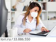 Купить «Female doctor in face mask working on laptop», фото № 33886550, снято 13 июля 2020 г. (c) Яков Филимонов / Фотобанк Лори