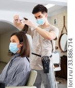 Купить «Man doing haircut for woman in salon using face masks», фото № 33886714, снято 1 июня 2020 г. (c) Яков Филимонов / Фотобанк Лори