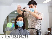 Woman client in mask during cuts hair at beauty salon. Стоковое фото, фотограф Яков Филимонов / Фотобанк Лори