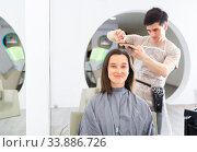 Купить «Woman client in during cuts hair at beauty salon», фото № 33886726, снято 3 июня 2020 г. (c) Яков Филимонов / Фотобанк Лори