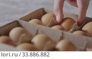 Купить «Hand taking out one egg from paper container on a kitchen table. Dolly slow motion, Full HD video, 240fps, 1080p. Step by step homemade dough preparation.», видеоролик № 33886882, снято 10 июля 2020 г. (c) Ярослав Данильченко / Фотобанк Лори