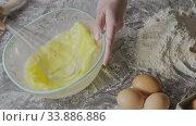 Купить «Whipping eggs in a transparent glass bowl by whisk on a flour background for preparation homemade cookies. Slow motion, Full HD video, 240fps, 1080p.», видеоролик № 33886886, снято 2 июля 2020 г. (c) Ярослав Данильченко / Фотобанк Лори