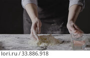 Купить «Woman hands pour water into flour and eggs to knead homemade gough for preparation pasta on a black background. Slow motion, Full HD video, 240fps, 1080p.», видеоролик № 33886918, снято 2 июня 2020 г. (c) Ярослав Данильченко / Фотобанк Лори