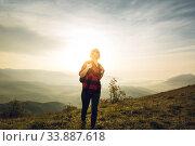 Купить «Девушка путешественник с рюкзаком гуляет на фоне природы», фото № 33887618, снято 2 мая 2019 г. (c) Сергей Тиняков / Фотобанк Лори