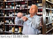Купить «Older man inspecting quality of red wine in wine store in search of perfect wine for solemn occasion», фото № 33887666, снято 11 июля 2020 г. (c) Яков Филимонов / Фотобанк Лори