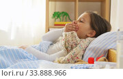 sick coughing girl lying in bed at home. Стоковое видео, видеограф Syda Productions / Фотобанк Лори