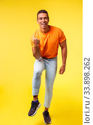 Купить «Vertical full-length cheerful sportsman in casual orange t-shirt, white pants, satisfied with excellent results, fist pump and smiling say yes as winning, achieve goal or prize, become champion.», фото № 33898262, снято 14 июля 2020 г. (c) easy Fotostock / Фотобанк Лори